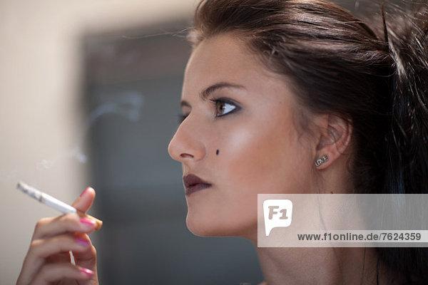 Teenage girl in dark makeup smoking