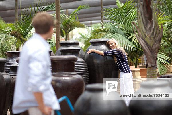 Frau umarmt große Pflanzgefäße