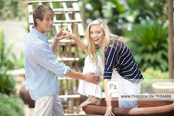 Mann hilft Freundin aus dem Pflanzgefäß