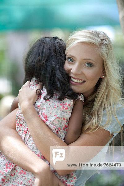Mutter umarmt Tochter im Freien