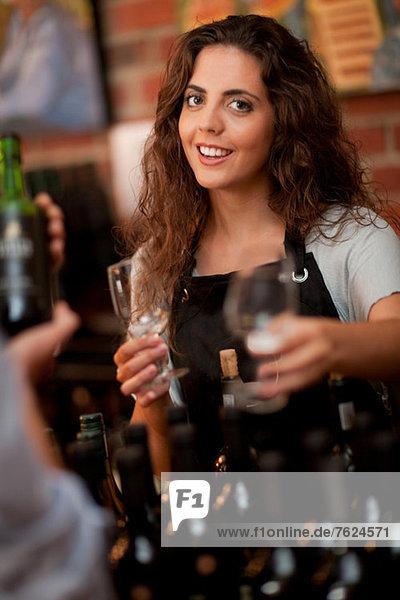 Server offering glass for wine tasting