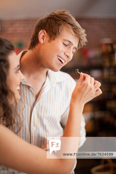 Couple tasting olives in grocery