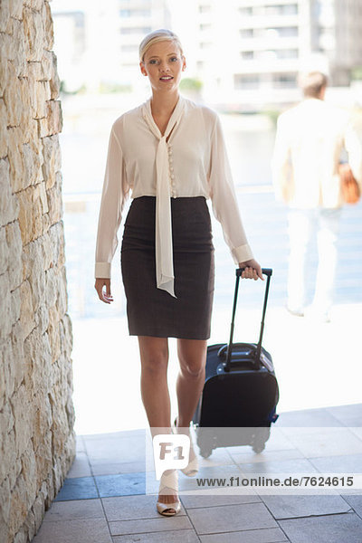 Businesswoman rolling luggage