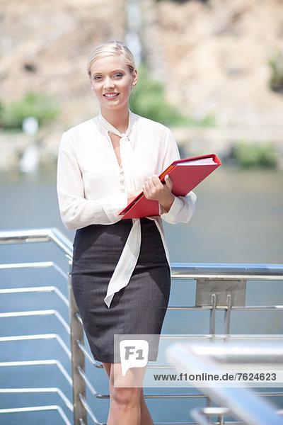 Geschäftsfrau mit Mappe auf dem Balkon