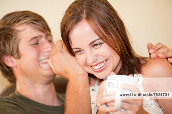 Mann flüstert in das Ohr der Freundin