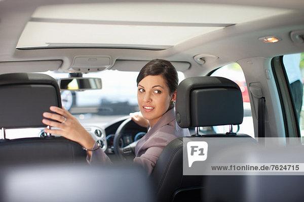 Frau beim Zurücksetzen im Auto