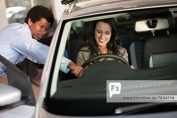 Verkäufer zeigt Frau neues Auto