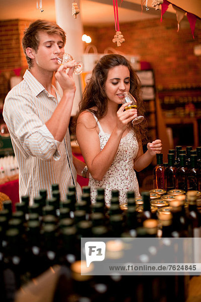 Couple tasting wine in grocery
