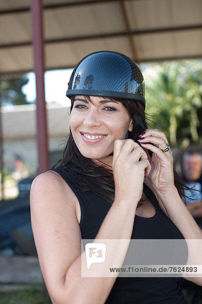 Woman tying on scooter helmet
