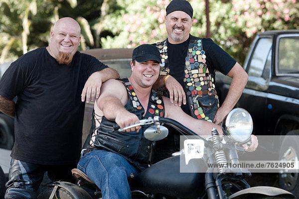 Männer lächeln um das Motorrad herum