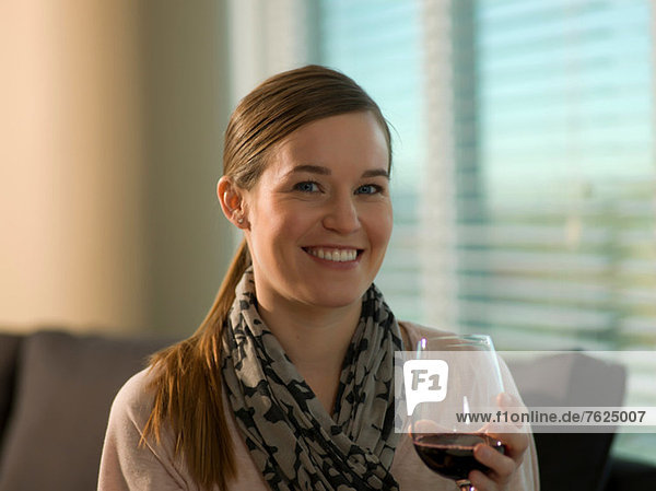 Smiling woman having glass of wine