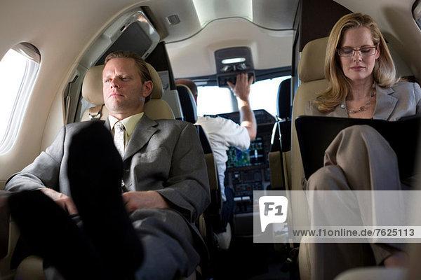 Geschäftsleute  die im Flugzeug arbeiten