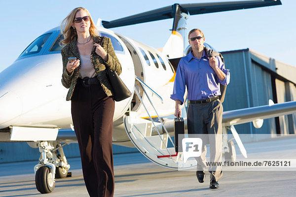 Geschäftsleute auf Flugzeugpiste
