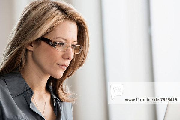 Geschäftsfrau mit Brille im Büro