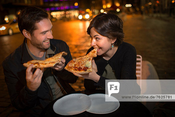 Paare essen Pizza auf der Stadtstraße
