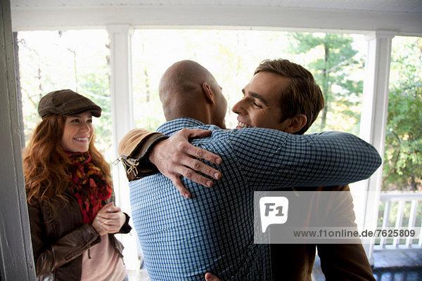 Männer umarmen sich vor der Haustür