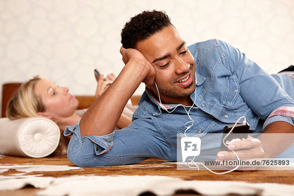Mann hört Kopfhörer im Bett
