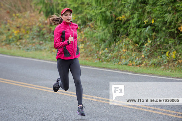 Frau läuft auf Landstraße
