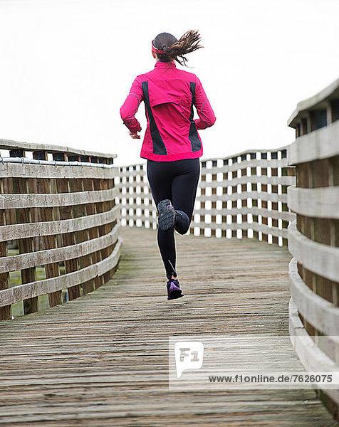 Frau läuft auf Holzdock