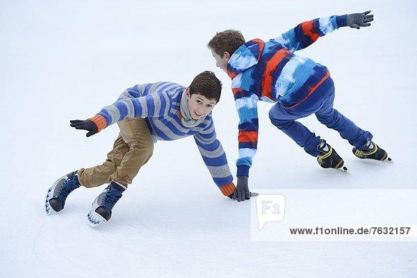 Zwei Jungen laufen Schlittschuh auf einem gefrorenen See Zwei Jungen laufen Schlittschuh auf einem gefrorenen See