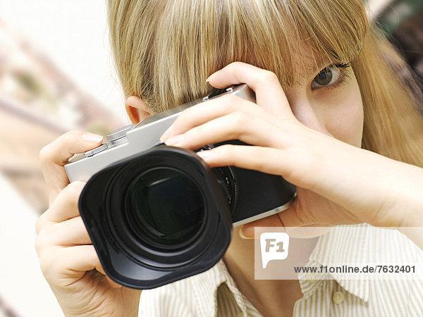 Frau mit Kamera fotografiert