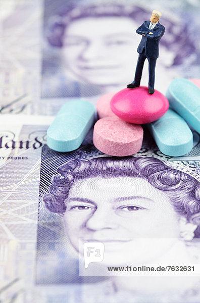 Miniatur-Figur eines Geschäftsmannes im Stand auf Pillen und einer Pfund Sterling-Banknote