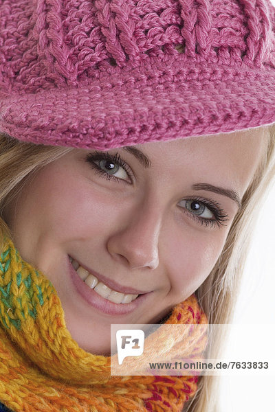 Smiling young woman wearing a colourful scarf and a pink knit cap  portrait