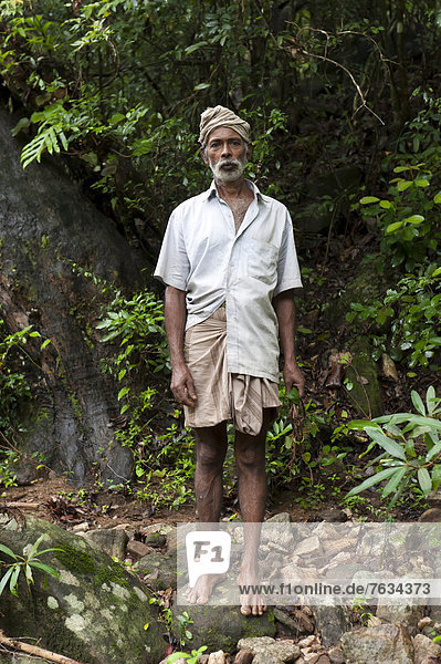 Barefoot villager standing in the jungle  Knuckles Range