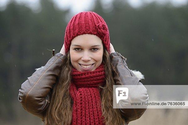 Lächelnde junge Frau mit Mütze und Schal  Porträt