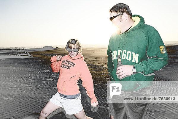 Vereinigte Staaten von Amerika  USA  Frau  Mann  Mensch  Amerika  Entspannung  Menschen  Strand  Küste  Natur  Spiel  Sand  ungestüm  Nordamerika  Außenaufnahme  Düne  Bier  Spaß  Oregon