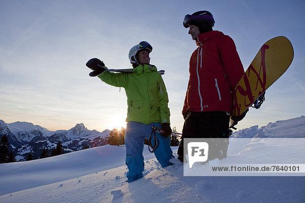 Frau Berg Winter Mann Snowboard Snowboarding Sonnenuntergang schnitzen Alpen Skisport Ski Außenaufnahme Tiefschnee Wintersport