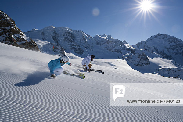 Frau Winter Mann schnitzen Skisport Ski Ansicht Kanton Graubünden Skipiste Piste Schotterstrasse Sonne Wintersport