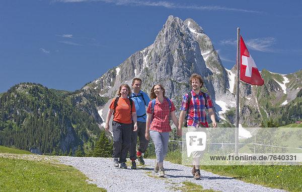 Schweizer Flagge Schweizer Flaggen Frau Berg Mann gehen Weg Touristin wandern Wanderweg trekking