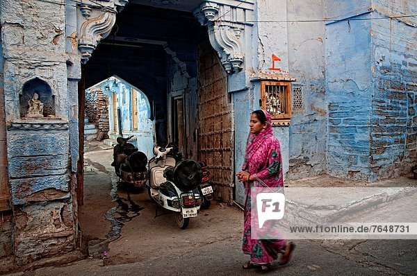 Woman passing in front of an entrance porch of blue painted residential haveli Jodhpur  Rajasthan  India