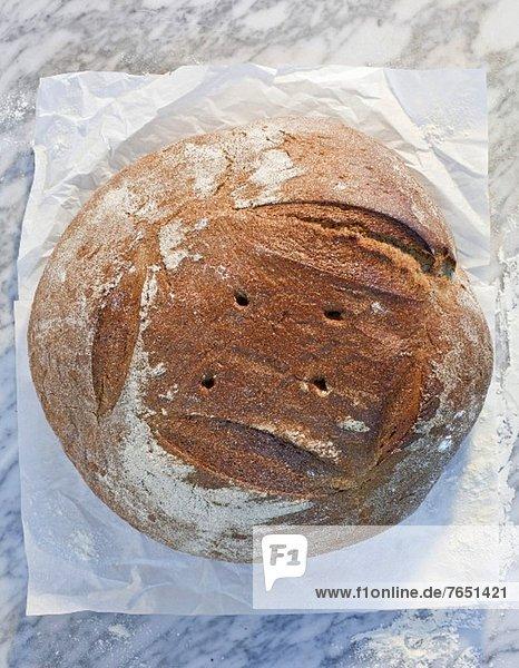 Brot auf Papier und Marmorplatte mit Mehl