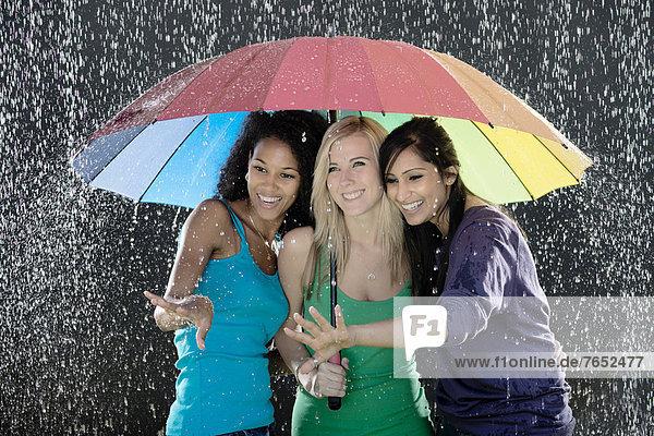 Farbaufnahme  Farbe  stehend  Zusammenhalt  Fröhlichkeit  Regenschirm  Schirm  unterhalb  Regen  Regenbogen