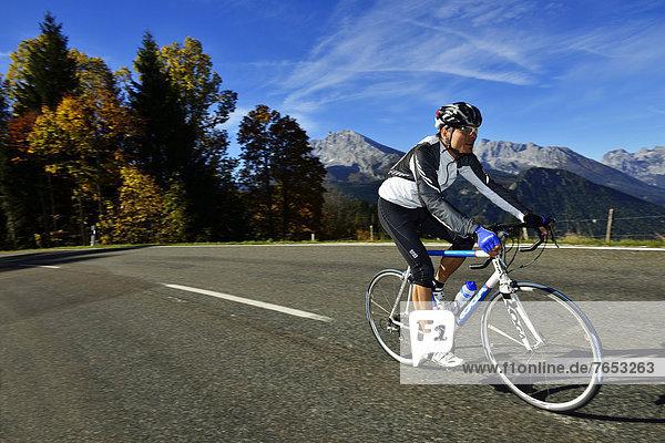 Cyclist riding along the Obersalzbergstrasse  Watzmann Mountain  Berchtesgaden  Upper Bavaria  Bavaria  Germany  Europe