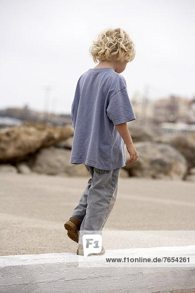 Junge balanciert auf einem Bordstein