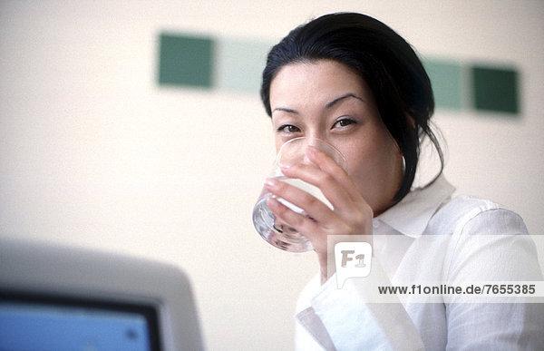 Junge Asiatin trinkt Wasser - Büro
