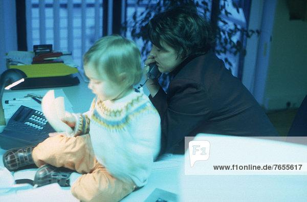 Telefonierende Frau mit Baby am Schreibtisch - Büro