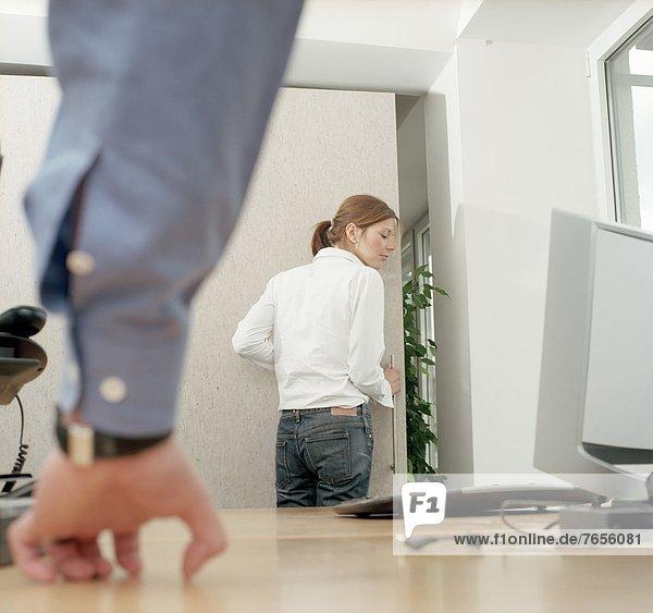 Frau verlässt Büro  Mann stütz sich auf Schreibtisch auf