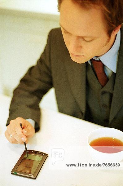 Geschäftsmann mit Palmtop und Tee