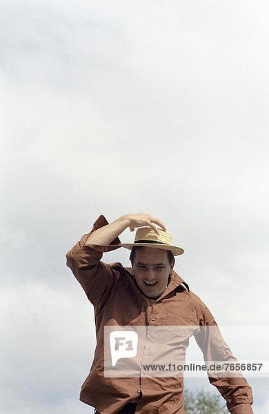 Ein Mann rennt und lacht  während er seinen aufgesetzten Hut mit einer Hand festhält - Freizeit