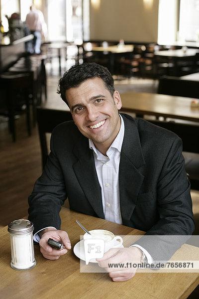 Geschäftsmann sitzt in einem Cafe bei einer Tasse Cappuccino