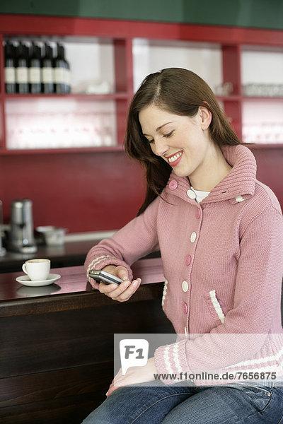 Frau sitzt an der Bar und liest SMS auf ihrem Handy