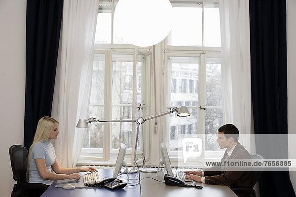 Geschäftsleute sitzen an gegenüberstehenden Schreibtischen