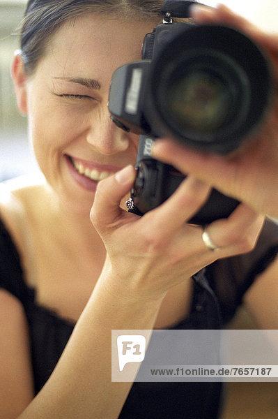 Junge brünette Frau macht fotografiert mit dem Objektiv Richtung Betrachter - Bilder - Hobby - Fotografie