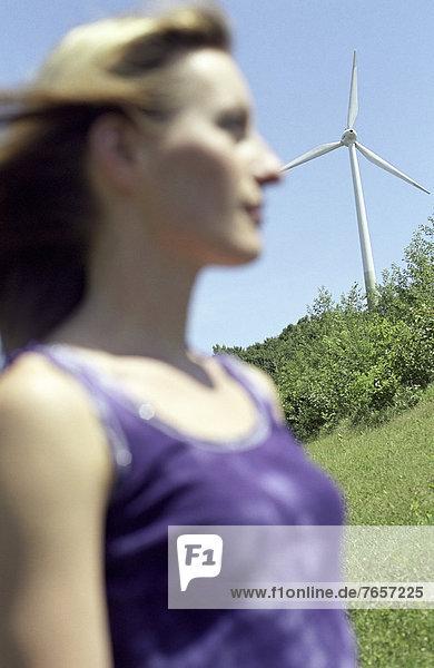 Blonde junge Frau steht vor einem Windrad - Pleasure - Wetter - Natur - Energie