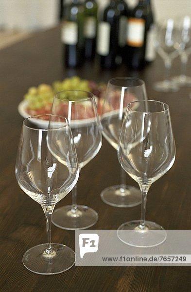 Vier Weingläser auf einem Tisch neben grünen Trauben - Alkohol - Genuss - Restaurant - Gastronomie