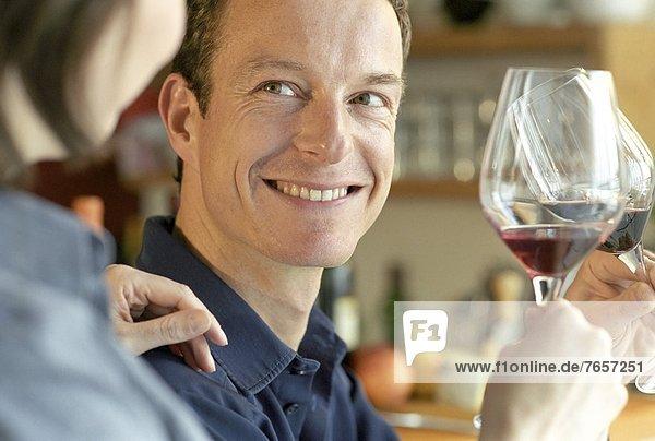 Mann und Frau stoßen mit zwei Gläsern Wein an - Feierlichkeit - Alkohol - Zweisamkeit
